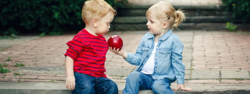 Kinder teilen Apfel