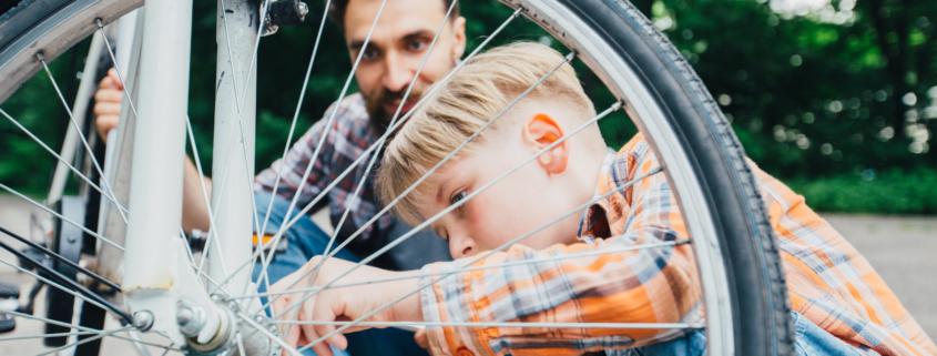 Vater repariert mit Sohn ein Fahrrad